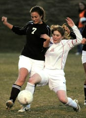 Henderson County's Lacey McConnell (7) battles Daviess County's Annie Elder (2) during the 2008 region soccer semifinal at Madisonville.