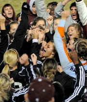 Henderson County's Tara Dance, center, is surrounded by teammates and fans as they sing the Colonel fight song after beating Daviess County 2-1 in two overtimes in the 2008 regional semifinals in Madisonville.