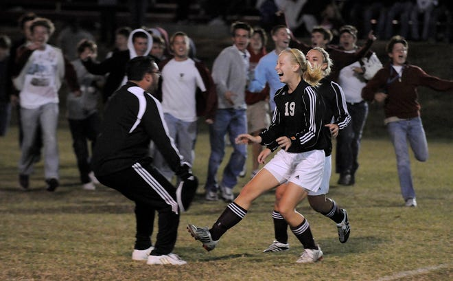 Henderson County assistant coach Shaun Soderling, left, prepares to embrace player Sara Garrett (19) as HCHS students rush the field after the Lady Colonels beat Daviess County 2-1 in two overtimes in the 2008 region semifinals in Madisonville.