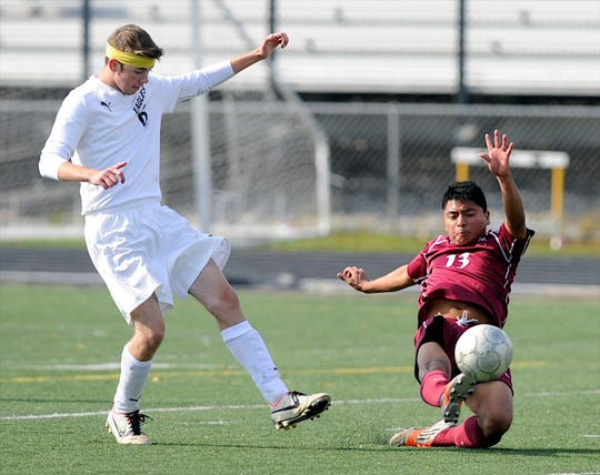Henderson County's Miguel Velazquez, right, shoots the ball as Johnson Central's Tyler Butcher, left, tries to block in during the 2013 state quarterfinal match in Lexington.