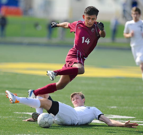 Henderson County's Waulder Gonzalez, top, clears Johnson Central's August Erikkson's tackle attempt during the 2013 state quarterfinals match in Lexington .