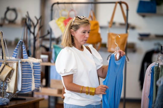 Melanie Gray looks at summer clothing inside the Mam'selle boutique store in Jackson, Tenn., Monday, May 18, 2020.