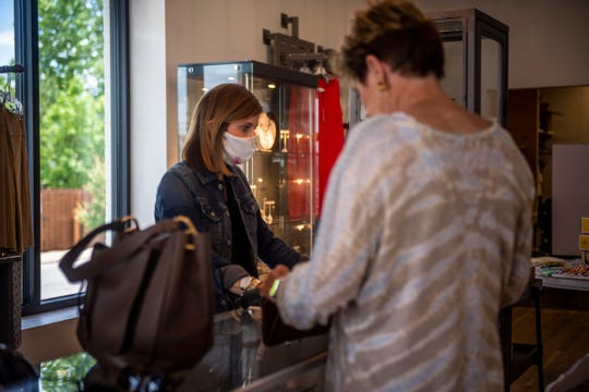 Kristy Long, visuals manager at Mam'selle, helps check out a customer on Monday, May 18, 2020. The boutique store has followed the guidelines of the CDC with employees wearing masks and sanitizing tables and countertops after each customer.