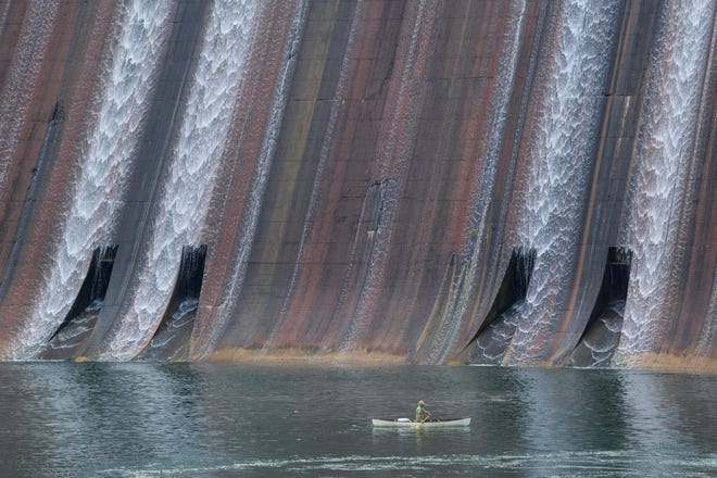 A fisherman canoes below Norris Dam on Sunday, May 17, 2020.