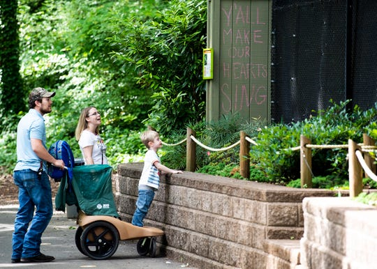 """A chalk message of """"Y'all make our hearts sing"""" is seen as guests enjoy exhibits at Zoo Knoxville on Monday, May 18, 2020. The zoo reopened to guests for passive use on Monday, and additional safety protocols like social distancing markers and hand sanitizer stations were put into place for its reopening."""