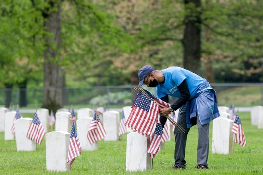 Marvin Blade, vice president of community relations for Duke Energy Indiana, places flags at the headstones of veterans at the Indiana Veterans' Home cemetery, Monday, May 18, 2020 in West Lafayette.