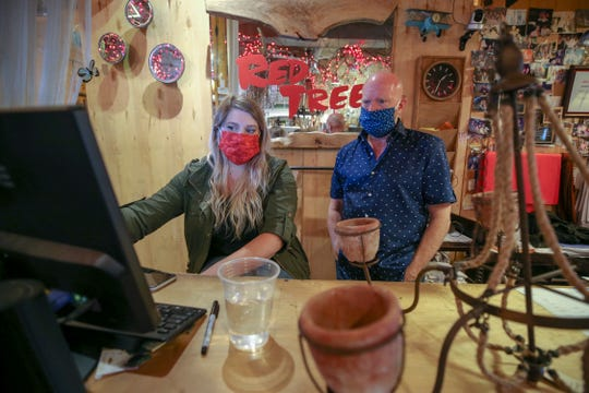 Diana Vono, left, and Red Tree owner, Garwood Linton, right, discuss wording on the Red Tree's website on Monday, May 18, 2020, in NuLu.  The store will reopen this week and have made multiple accommodations to handle social distancing.