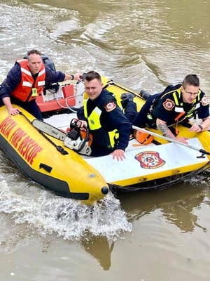 Delta Township firefighters rescued two people stranded in the Grand River after their canoe capsized.