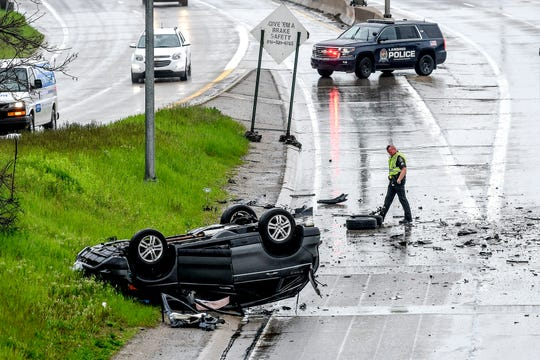 Lansing police investigate the scene of a multiple-vehicle crash on westbound I-496 at the Grand Avenue exit on Monday, May 18, 2020, in Lansing.