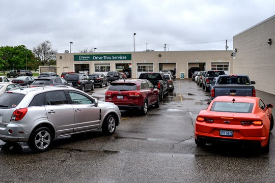 Vehicles line up at Sparrow Health System's drive-through COVID-19/antibodies testing site at the former Sears Auto Center in the Frandor shopping center on Monday, May 18, 2020, in Lansing. Lines for the testing reached Michigan Avenue during parts of the day.