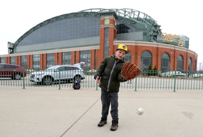 Liam Lamphear watches the ball fall past his glove as he plays catch with his mother Randi Lamphear outside Miller Park in Milwaukee on what would have been Liam's first opening day game.