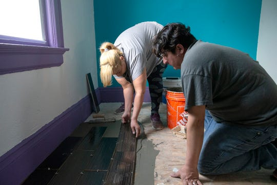 Sheila DeCuevas and her husband Nabor Cuevas Tirado put down tiles in their house at the North 7th Street. For families that purchase distressed homes to fix them up, Acts Housing provides a counselor on the rehabilitation process.