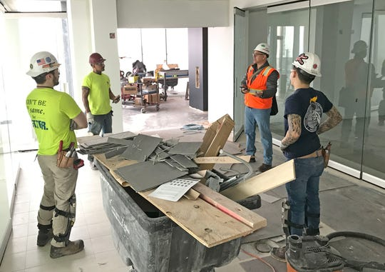Workers with Lippert Flooring and Tile, out of Menomonee Falls, have a discussion at a socially safe distance due to the coronavirus on the 35th floor of the new BMO Tower located on N. Water St. in Milwaukee.