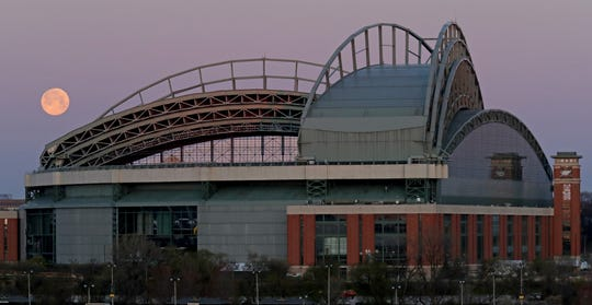 A full super moon sets behind Miller Park, home of the Milwaukee Brewers. Major League Baseball may return this summer.