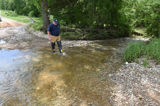 Buford Fire Chief Will Syfrett crosses a wet weather creek on Newts Road in the Four Corners area Monday. On Saturday, water raging down the creek would have been up to Syfrett's chest in this photograph, according to debris lines in the area. A man tried to cross the creek Saturday and had to be rescued after his truck was washed downstream.