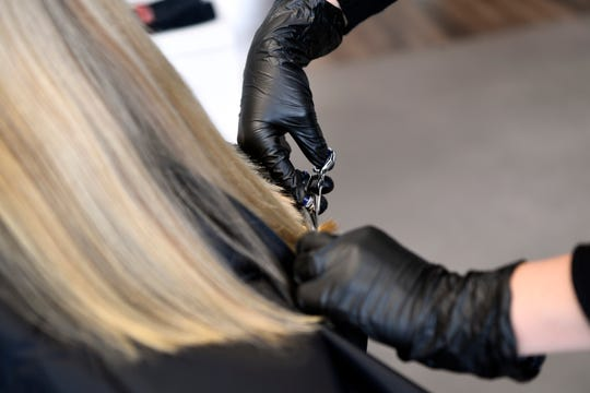 Stylist Samantha DeFalco cuts Valerie Panza's hair with gloves on in Panico Salon and Spa in Ridgewood on Monday, May 18, 2020.