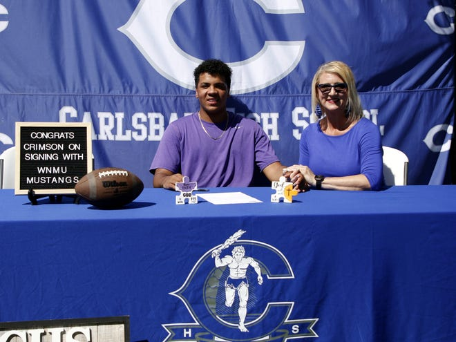 Carlsbad senior Crimson McKenzie signs his letter of intent to attend college at Western New Mexico University with his mother Bonnie McKenzie on May 18, 2020. McKenzie was the starting center for the Cavemen the last two seasons, not missing a single first-team snap this year.