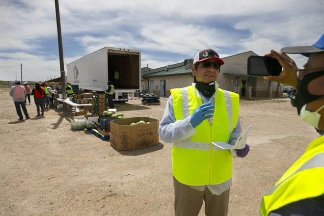 Jared Touchin (right), communications director of the Navajo Nation Office of the President and Vice President, records a video of Navajo Nation President Jonathan Nez (center) as food is distributed to community members at a food distribution point before the start of a weekend-long curfew in Coyote Canyon, New Mexico, on the Navajo Nation, on May 15, 2020.