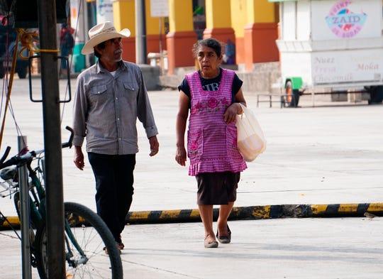 """Una pareja de indígenas son vistos mientras caminan, hoy lunes al iniciar su """"nueva normalidad"""", en el municipio de Ejutla estado de Oaxaca."""