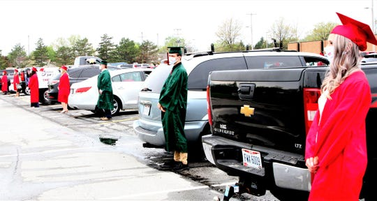 Graduates stand by their vehicles preparing for the graduation events at Oak Harbor High School on Sunday where the seniors were donning their masks.