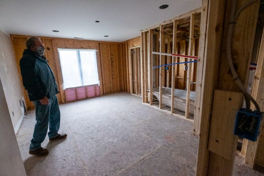 Kirk Harms, a field supervisor for LaDuke Construction, walks through a home in the process of being renovated Monday, May 18, 2020, in Fort Gratiot. The coronavirus pandemic and associated lockdown paused all services deemend non-essential, which put a pause on construction projects across the state.