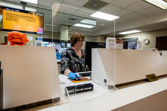 Joanne Lamar, a teller at Eastern Michigan Bank, works behind a plexiglass shield Monday, May 18, 2020, in Port Huron. Once the bank reopens their lobby, the plexiglass will remain on desks and the tellers' stations.