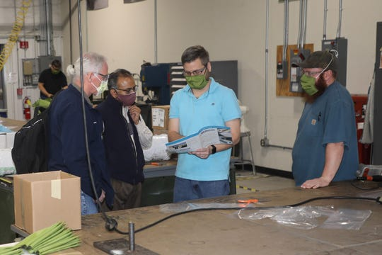 Shawn Hind, Letterkenny Army Depot (center) discusses isolation gown materials with (from left) James Eichelberger, WellSpan, Srinath Asuri, WellSpan, and Logan Robinson, LEAD at the LEAD upholstery shop on April 22, 2020. LEAD is currently producing personal protective equipment (PPE) for WellSpan to help combat COVID-19.
