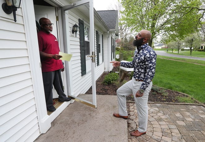 Lincoln Calip of Triple C's Commercial & Residential, confers with  customer Willie Dilworth about work outside his Greece home.  Contractors are getting back to work as the state begins to slowly reopen from the coronavirus shutdown.