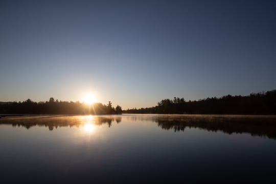 The sun rises over Old Forge Pond on Wednesday, May 13, 2020.