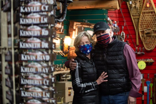 Katie Boesche and Chip Kiefer, owners of Souvenir Village in Old Forge, New York, smile behind their masks for a photo on Tuesday, May 12, 2020. Their store has been closed since mid-March due to the coronavirus pandemic.