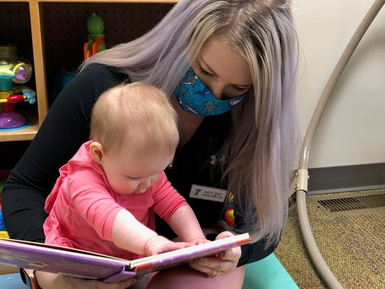 Katie Qazi, director of the Eastside YMCA Child Care Center at the Fairport Baptist Homes, reads with 8-month-old Madelyn.
