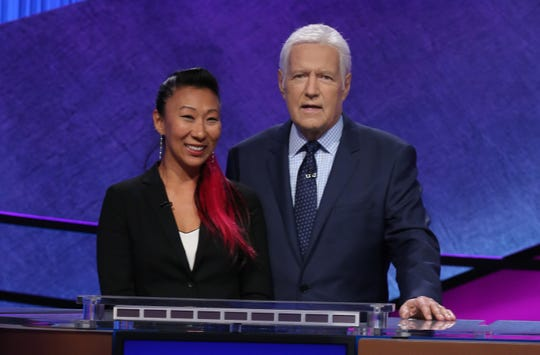 Jenna Hall stands at the podium with Alex Trebek, host of Jeopardy!