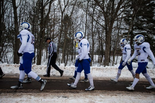 Angelo State University football players and a NCAA referee take a 6-minute walk from the locker room to the field before their NCAA Division II first-round playoff game against Michigan Tech in Houghton, Michigan, on Nov. 22, 2014.