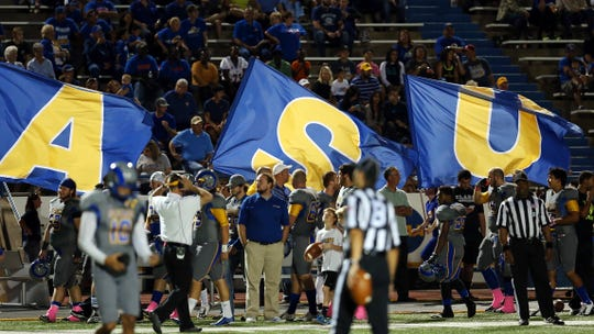 Angelo State University cheerleaders run flags down the field after an ASU touchdown against Eastern New Mexico on Oct. 25, 2014.