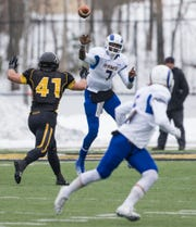 Angelo State's Kyle Washington passes to Dakarai Pecikonis while under pressure during their NCAA Division II first-round playoff game against Michigan Tech in Houghton, Michigan, on Nov. 22, 2014.