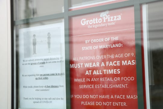 Warnings about social distancing and other safety measures at taped to the main entrance of the Grotto Pizza in Ocean City on May 18, 2020.