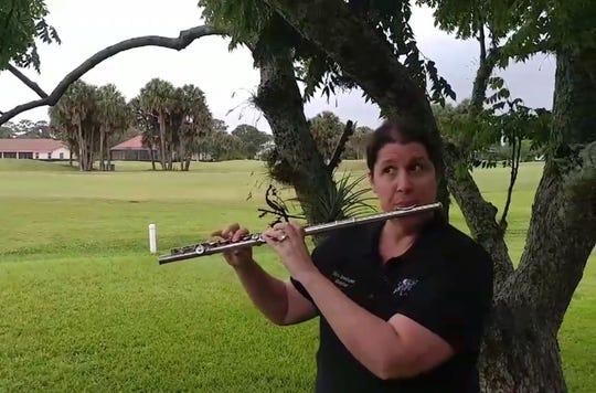 Music teacher Amy Isenhower plays the flute Friday.