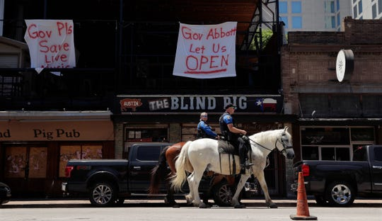 Austin police officers on horseback pass signs hanging on a pub directed at Texas Gov. Greg Abbott on Monday, May 18, 2020, in Austin. Texas continues to go through phases as the state reopens after closing many non-essential businesses to help battle the spread of COVID-19. Bars will be allowed to reopen with capacity limits in most parts of the state starting Friday, May 22, 2020.