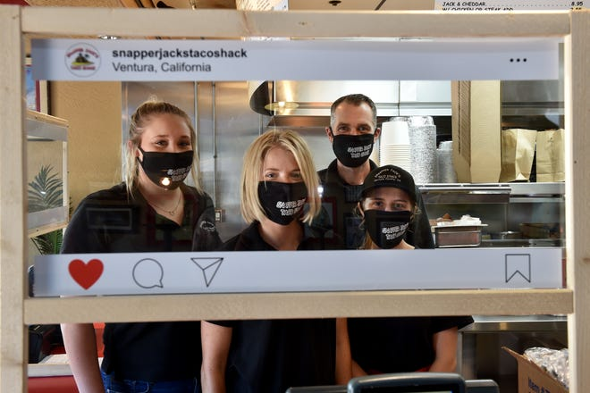 From left, Kelsey Phipps, Isabella Norris, Jarrid Smith and Shay Swaney of Snapper Jack's Taco Shack pose inside a Plexiglass barrier made to look like an Instagram screen at the restaurant's Telegraph Road location in Ventura. To celebrate the Ventura County-based chain's 20th anniversary in the midst of the coronavirus pandemic, Smith, the general manager, asked an employee to make a TikTok video about its takeout menu and curbside pickup. The video went viral, garnering more than 8000 views when reposted on Instagram.
