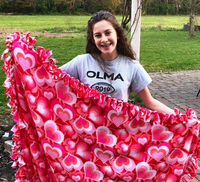 Carlina Fiocchi, a freshman at Our Lady of Mercy Academy, displays a blanket she made for a displaced child as part of the OLMA Interact Club's Charitable Challenge. OLMA is offering virtual information sessions for prospective students and their families since the campus is currently closed because of COVID-19.