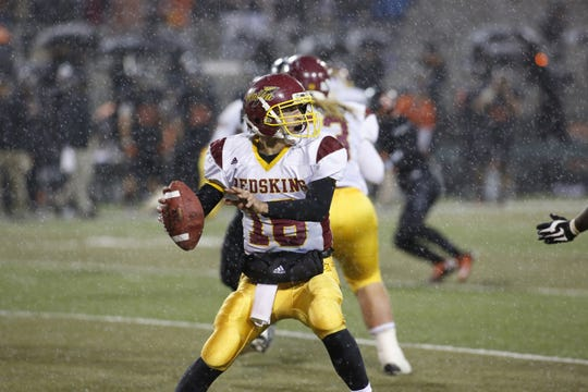 Tulare Union's Oscar Reyes (16) drops back for a pass in the rain against Central at Koligian Stadium in 2012.