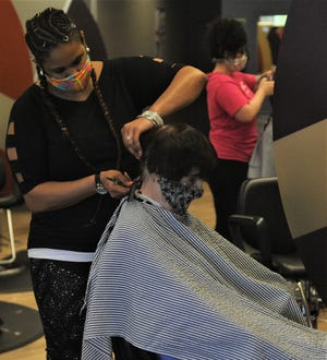 Shaniqua Norris, a stylist at Great Clips, trims Delores Efaw's hair. Customers are required to wear masks at Great Clips so the business can meet health protocols.