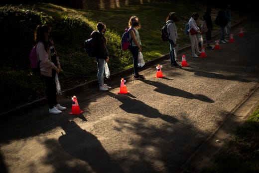 Students stand next to cones to mark social distancing as they wait in line before entering the classroom at Les Magnolias primary school during the partial lifting of COVID-19, lockdown regulations in Brussels, May 18, 2020. Belgium is taking the next step in its relaxation of the coronavirus lockdown on Monday, with more students going to school, markets and museums reopening