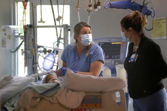 FILE - In this May 8, 2020, file photo, registered nurse Katie Hammond, left, works with another nurse on a patient in the COVID-19 Intensive Care Unit at Harborview Medical Center , in Seattle. The number of deaths in Washington because of the coronavirus has reached 1,000, the Washington State Department of Health reported Saturday, May 16, 2020. The agency added eight more deaths and listed the total number of confirmed cases at 18,288. (AP Photo/Elaine Thompson, File) ORG XMIT: WAET202