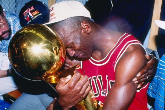 Michael Jordan hugs the NBA championship trophy after defeating the Los Angeles Lakers in the 1991 NBA Finals.