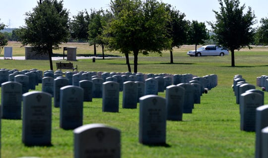 A hearse drives past gravestones at Texas State Veterans Cemetery at Abilene.