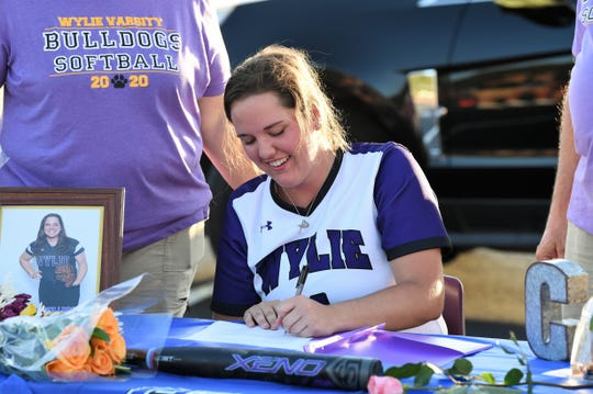 Bailey Buck signs with Cisco College during the Wylie softball Senior Night drive-thru celebration in the WHS parking lot on Monday, May 18, 2020. The Lady Bulldogs celebrated their six seniors who had their final season canceled due to the coronavirus pandemic.