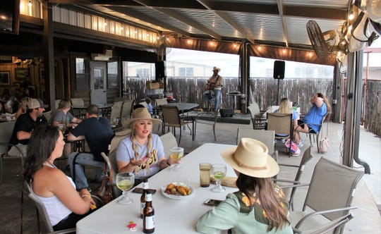 Those enjoying dinner, drinks and the music of Blan Scott are spread out on the patio of Lytle Land & Cattle Co.