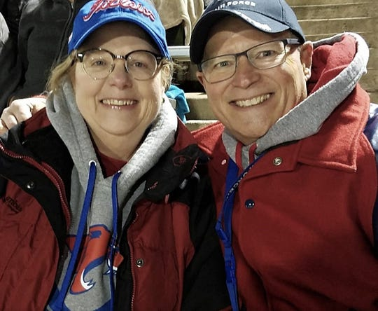 Caela and Steve Shinkle cuddle at a Cooper football game in November. They have been married for 25 years.