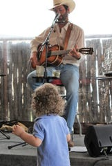 Denver Doan gets a good look and listen to singer-musician Blan Scott during Scott's show Friday at Lytle Land & Cattle Co. Scott is back at the mic Friday.